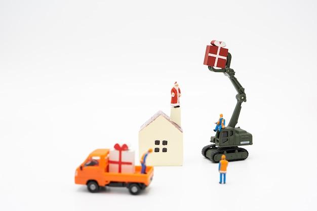 Die miniaturleute, die auf weihnachtsbaum stehen, feiern weihnachten