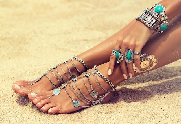 Die mit armbändern und ringen verzierte hand der frau ruht auf den beinen, die mit schmuck im boho-stil bedeckt sind. die frau sitzt in entspannter position am tropischen sandstrand. körperteile sommertrends