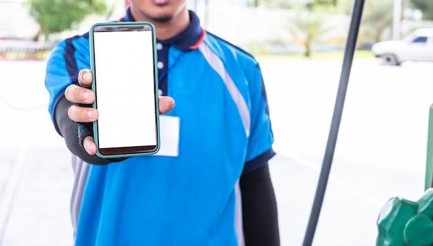 Die mitarbeiter der tankstelle halten ein smartphone in der hand, um online-zahlungen oder -transaktionen zu ermöglichen.