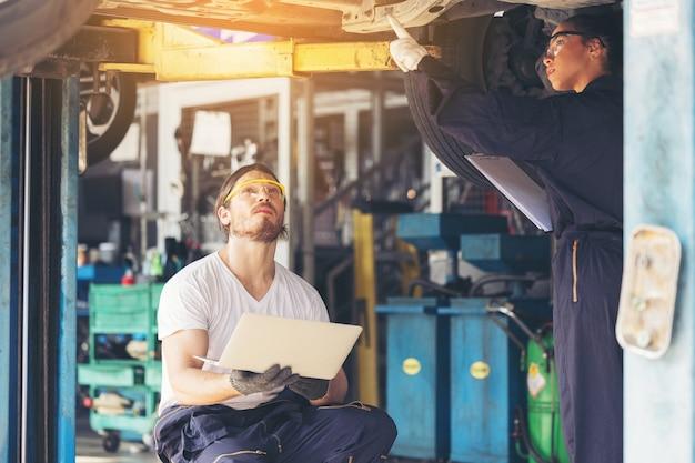 Die mitarbeiter des autoservices überprüfen die boden- und unterfahrschutzplatten unter dem angehobenen auto
