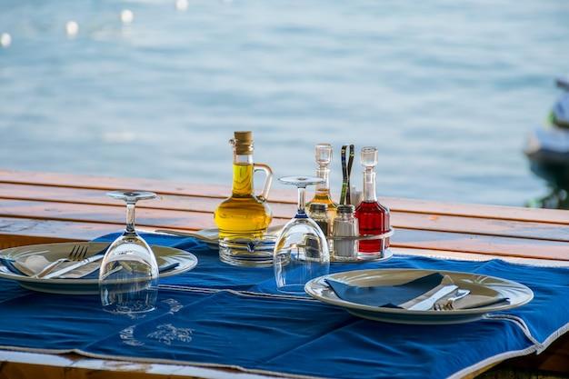 Die mitarbeiter des restaurants bereiteten ihre tische in der nähe des meeres zum abendessen während des sonnenuntergangs vor