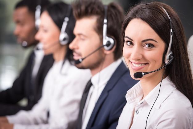 Die mitarbeiter lächeln und arbeiten an computern.