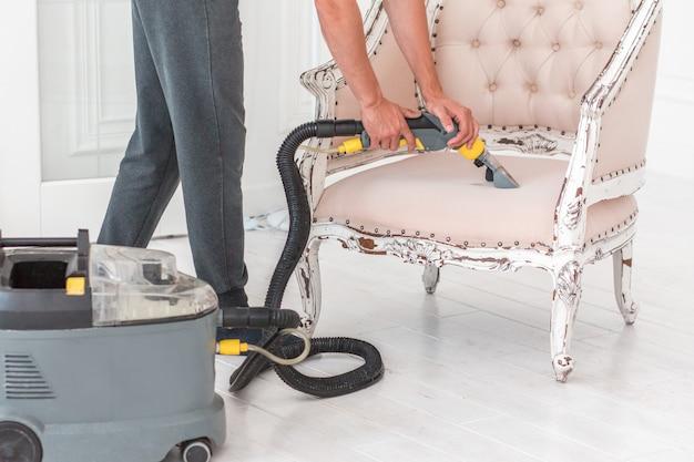 Die mitarbeiterhand der reinigung säubert das klassische sofa mit professioneller extraktionsmethode.