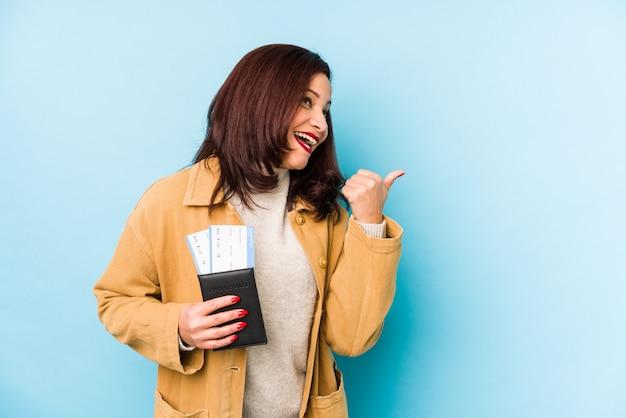 Die mittelalterfrau, die einen pass hält, zeigt mit dem daumenfinger weg, lachend und sorglos.