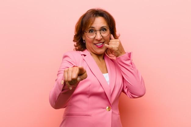 Die mittelalterfrau, die nett lächelt und auf kamera zeigt, während ein anruf sie später macht, gestikulieren und sprechen am telefon gegen rosa wand