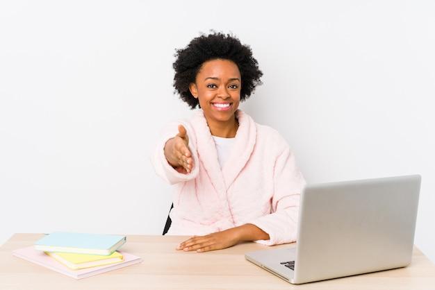 Die mittlere gealterte afroamerikanerfrau, die zu hause arbeitet, lokalisierte das ausdehnen der hand an der kamera in der grußgeste.
