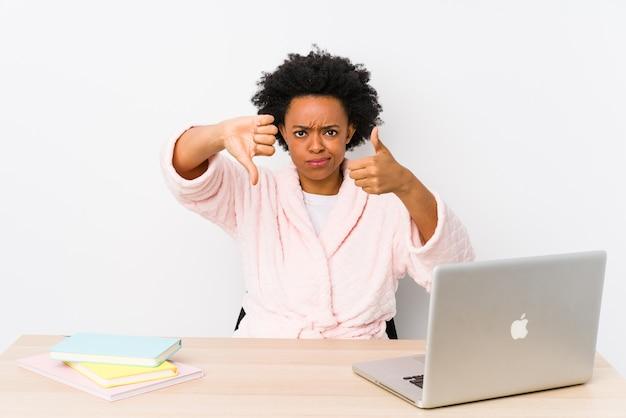 Die mittlere gealterte afroamerikanerfrau, die zu hause arbeitet, lokalisierte das zeigen von daumen hoch und von daumen unten, wählen schwieriges konzept