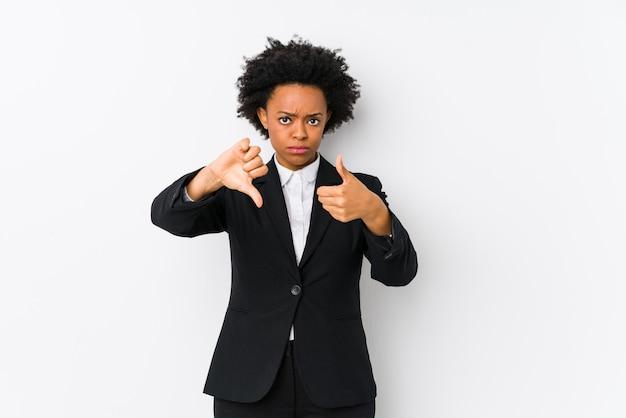 Die mittlere gealterte afroamerikanergeschäftsfrau gegen eine weiße wand, die lokalisiert wird, daumen hoch und daumen unten zeigend, wählen schwierig konzept