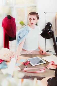 Die modedesignerin, die im studio arbeitet, sitzt auf dem schreibtisch