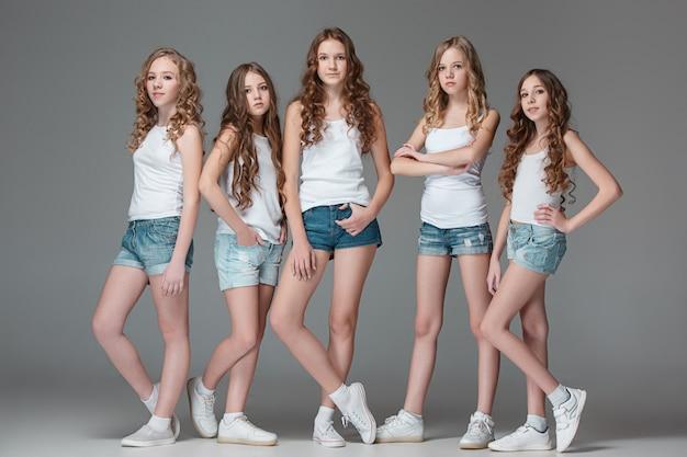 Die modemädchen, die zusammen stehen und kamera über grauem studiohintergrund betrachten