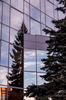 Die moderne fassade des bürogebäudes ist ein abstraktes fragment mit glänzenden fenstern in einer stahlkonstruktion. toller hintergrund für eine visitenkarte, einen flyer, ein banner mit platz für eine inschrift oder ein logo