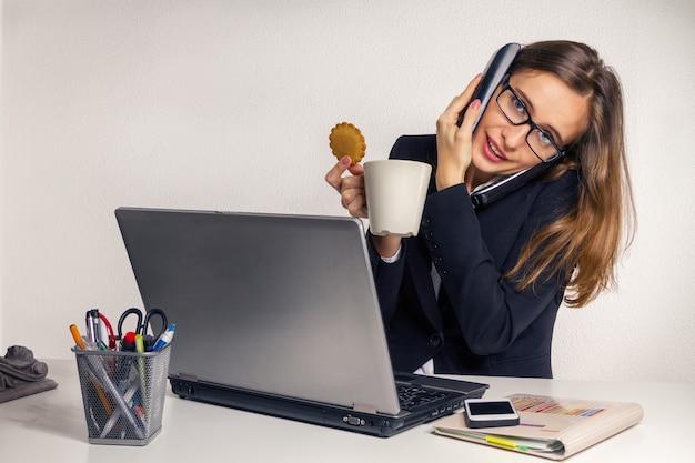 Die moderne frau mit kaffeepause mit keksen im büro in der arbeitszeit