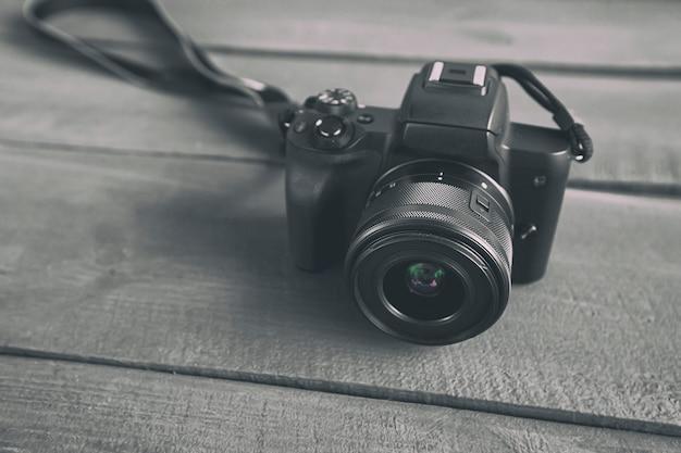 Die moderne spiegellose kamera auf dem holzschreibtisch