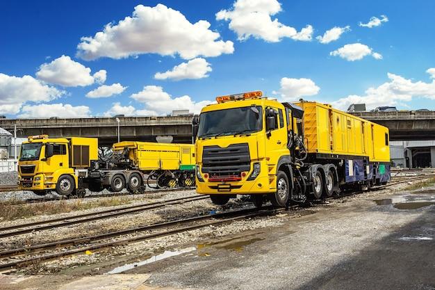 Die modernen gelben schienen, die den maschinenwagen warten, stehen bereit, um die schiene mit blauem himmel zu warten.