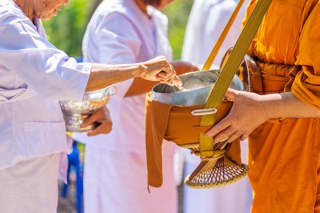 Die mönche des buddhistischen sangha (geben einem buddhistischen mönch almosen),