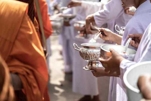 Die mönche des buddhistischen sangha (geben einem buddhistischen mönch almosen)