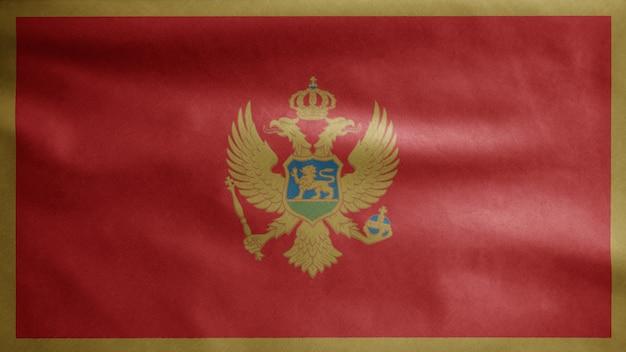 Die montenegrinische flagge weht im wind. montenegro banner weht, weiche und glatte seide. stoff textur fähnrich hintergrund