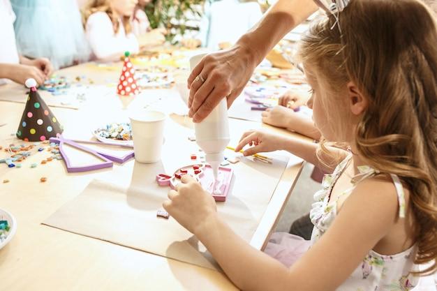Die mosaik-puzzle-kunst für kinder, kreatives spiel für kinder. die hände spielen mosaik am tisch. bunte mehrfarbige details schließen. kreativität, kinderentwicklung und lernkonzept