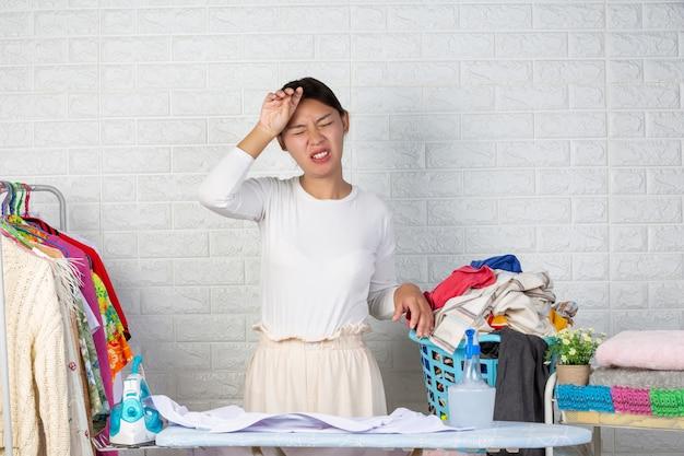 Die müde hausfrau hat die kleider im korb mit dem weißen backstein satt.