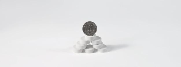 Die münze steht auf einem berg von pillen, isoliert auf einem weißen hintergrund, kopienraum.