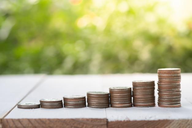 Die münzen, die mit wachsender anlage auf grün stapeln, verwischten hintergrund und sonnenlicht es ist gebrauch für die einsparung und langfristige investition