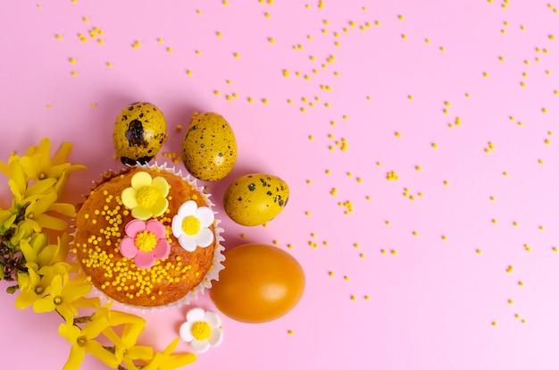 Die muffins, die mit verziert werden, besprüht, blumen des mastixes und gelbe ostern-wachteleier auf pastellrosahintergrund.