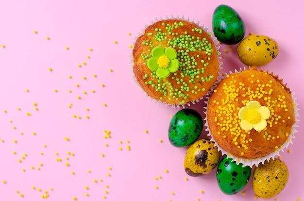 Die muffins, die mit verziert werden, besprüht, blumen von mastix-, grünen und gelbenostern-wachteleiern auf pastellrosahintergrund.