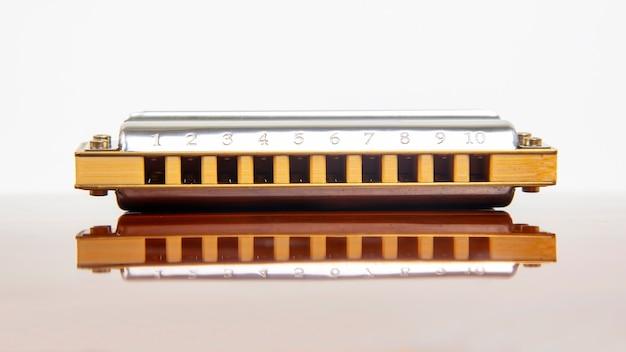 Die mundharmonika liegt auf einer verspiegelten oberfläche. klassisches musikblasinstrument.