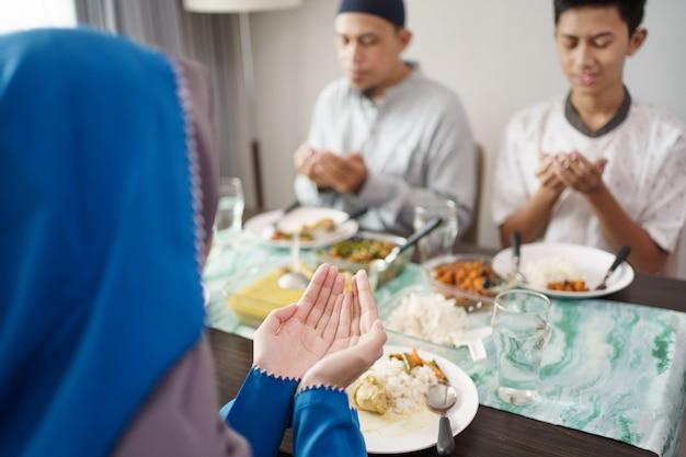 Die muslimische familie betet zusammen vor dem essen