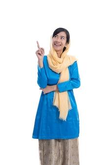Die muslimische frau, die blau trägt, schaut auf und denkt, um raum zu kopieren