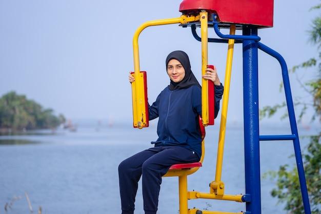 Die muslimische frau, die dunkle kleidung und hijab trägt, deckt ihre haarübungen nach körpergewicht ab.