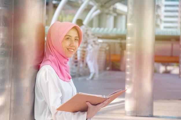 Die muslimische frau liest ein buch. sie lächelt.
