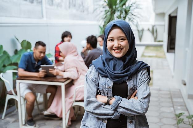 Die muslimische frau verschränkte lächelnd den arm