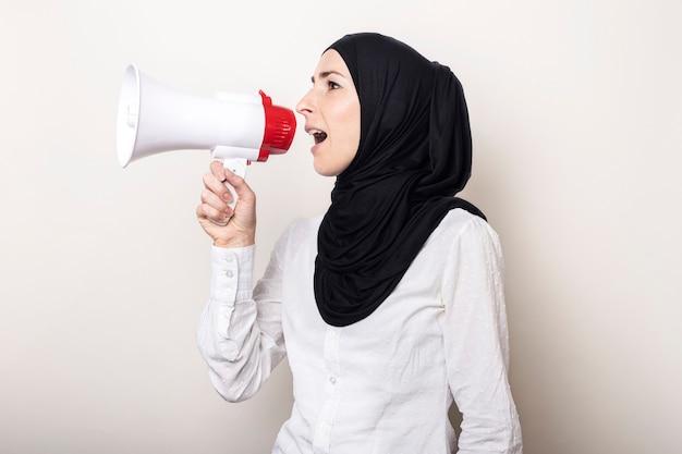 Die muslimische junge frau im hijab hält ein megaphon in den händen und schreit hinein