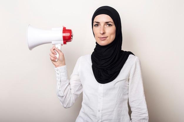Die muslimische junge frau im hijab hält ein megaphon in den händen