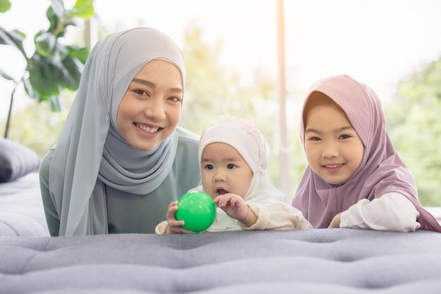 Die muslimische mutter im hijab ist ihre kleine tochter, die im wohnzimmer sitzt