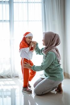Die muslimische tochter gibt sich die hand und küsst die mutter, bevor sie zur schule geht