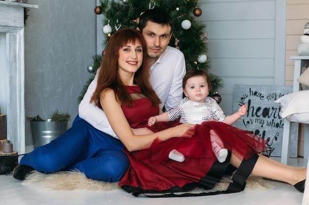 Die mutter, der vater und die tochter, die nahe weihnachtsbaum sitzen