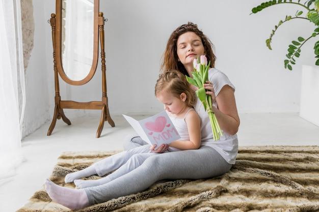 Die mutter, die frische tulpe riecht, blüht, während die tochterlesegrußkarte sitzt, die auf weichem teppich sitzt