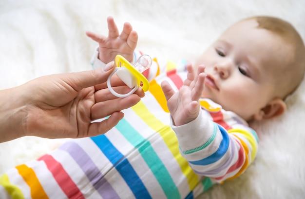 Die mutter gibt dem baby einen schnuller. selektiver fokus. kind.