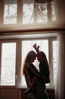 Die mutter hält das mädchen, sie stehen am fenster, tanzen, umarmen, lieben und sorgen sich, familie