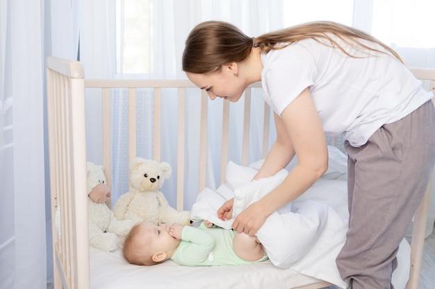 Die mutter legt das baby ins bettchen und deckt es mit einer decke zu