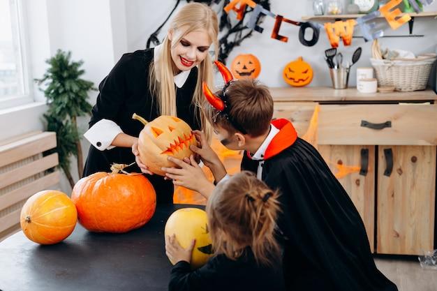 Die mutter und kinder, die kürbis halten und haben lustige zeit zu hause. halloween