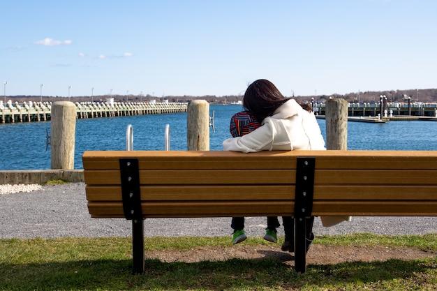 Die mutter und sohn, die auf einer bank sitzen, betrachten die ozeanlandschaft