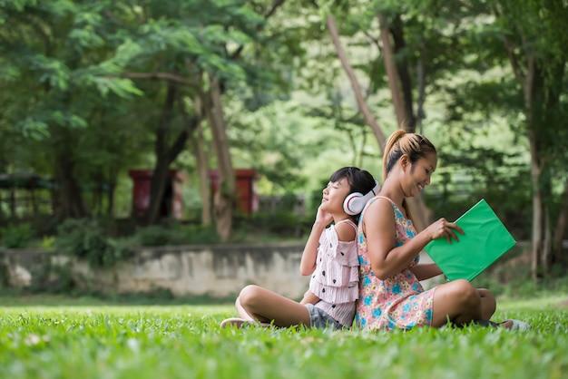 Die mutter und tochter, die märchen zu ihrer tochter lesen, hören ton mit kopfhörer im park