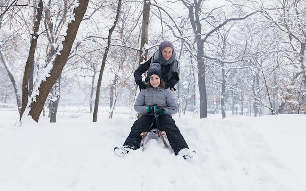 Die mutter und tochter, die schlitten genießen, fahren in wald am wintertag