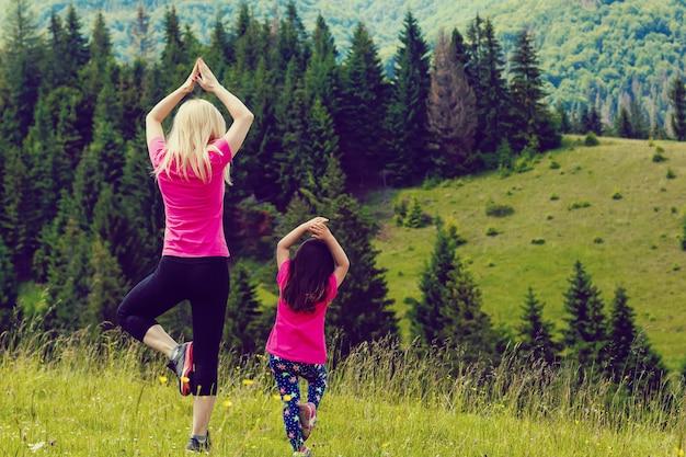 Die mutter und tochter, die yoga baum tun, werfen oben auf berg auf