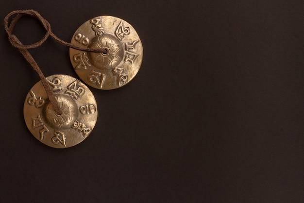 Die mystische tibetische karatal-meditation aus bronze liegt auf einem kontrastierenden schwarzen boden. tibetische klingelplatten