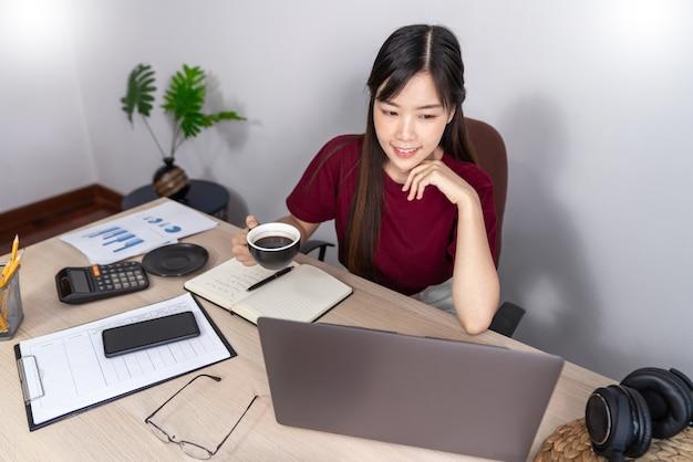 Die nachdenkliche asiatische frau entspannt sich auf dem desktop und arbeitet von zu hause aus