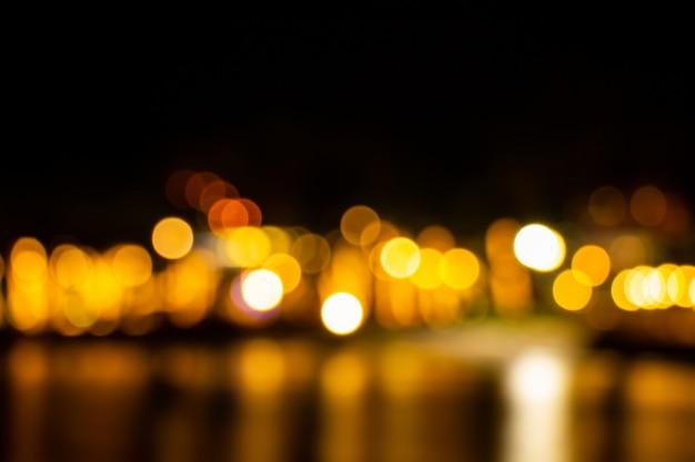 Die nachtdämmerung verwischte das helle goldbokeh, das über den abstrakten hintergrund des meeresoberflächenwassers nachdenkt